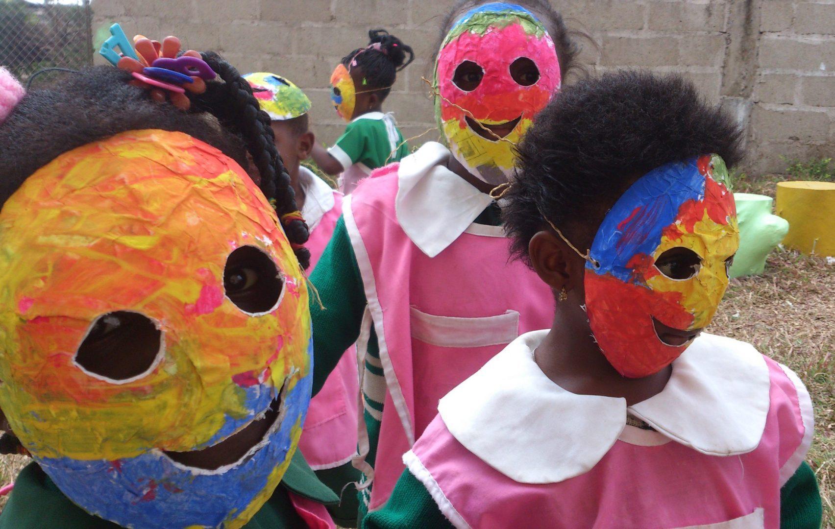 children wearing colourful paper mache masks